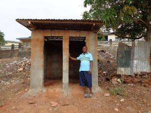 Pastor James in front of toilets